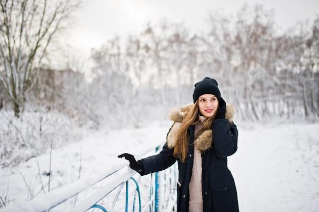 Belle fille brune en vêtements chauds d'hiver. modèle sur veste d'hiver et chapeau noir.