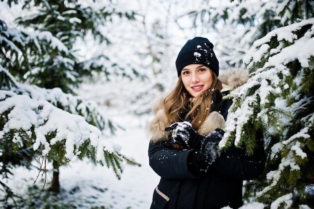 Belle fille brune en vêtements chauds d'hiver. modèle sur la veste d'hiver et un chapeau près des pins.