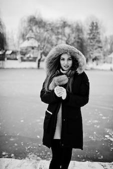 Belle fille brune en vêtements chauds d'hiver. modèle sur veste d'hiver contre lac gelé au parc.