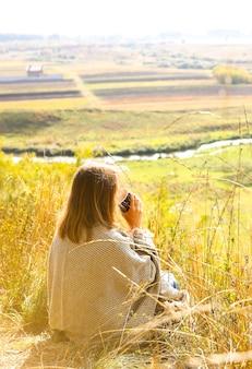 Belle fille buvant du café dans la nature d'automne. une tasse avec boisson chaude dans les montagnes. ambiance chaleureuse. feuilles rouges et jaunes. auto-isolement pendant le temps de quarantaine. pensez à la vie.