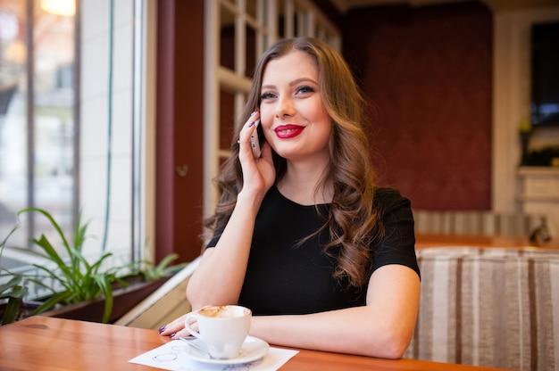 Belle fille buvant du café et parler au téléphone