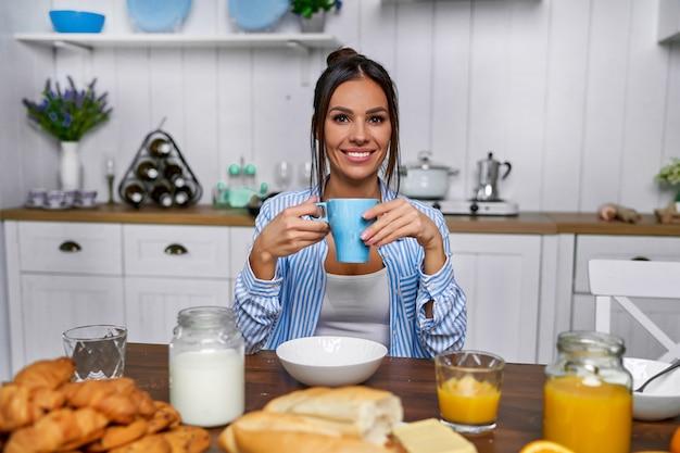 Belle fille buvant du thé à la maison dans la cuisine