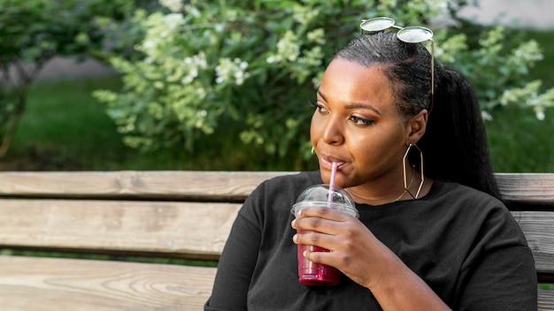 Belle fille buvant un smoothie à l'extérieur