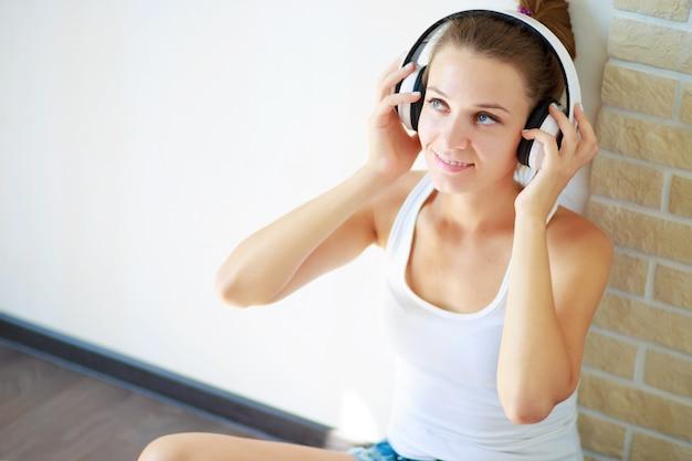 Belle fille avec un casque d'écoute de la musique assis sur le sol