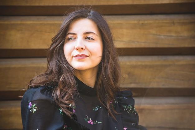 Belle fille caucasienne aux cheveux noirs sourit contre un mur en bois.