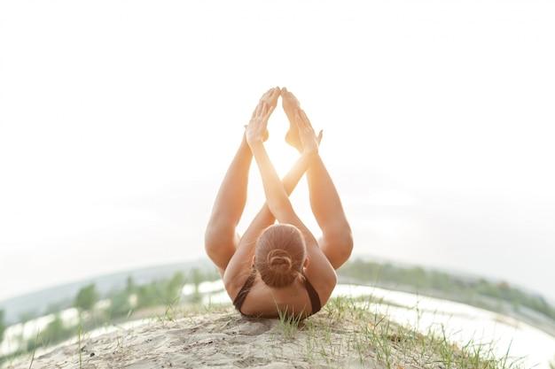 Une belle fille caucasienne dans un maillot de bain noir faire du yoga position sur la nature
