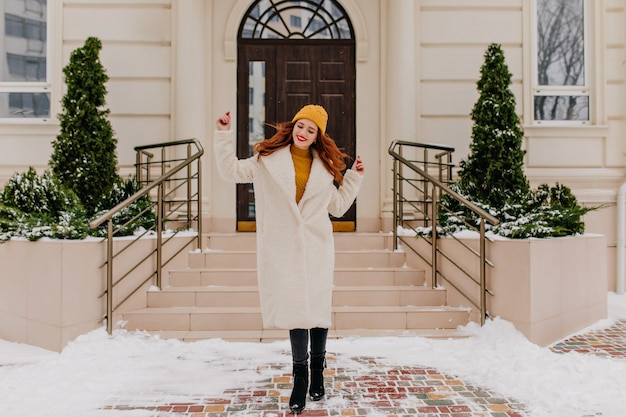 Belle fille caucasienne dansant le matin d'hiver. portrait en plein air d'une femme au gingembre blithesome porte un chapeau et un manteau.