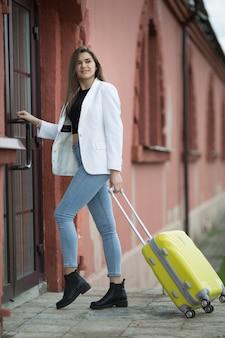 Belle fille caucasienne avec une grosse valise jaune.