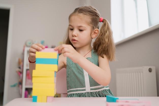 Belle fille caucasienne jouant avec des blocs multicolores en bois