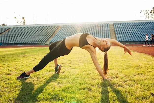 Belle fille caucasienne sportive, faire des exercices à l'extérieur.