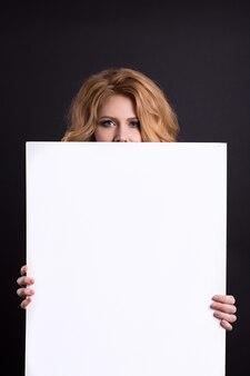 Belle fille caucasienne tenant un blanc vide, une place pour la publicité