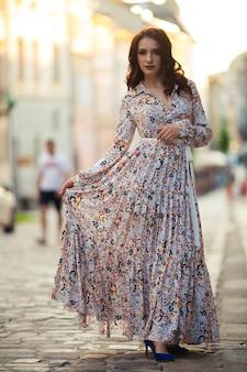 Belle fille sur un champ de fleurs dans une belle robe