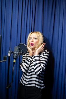 Belle fille chantant dans un studio d'enregistrement