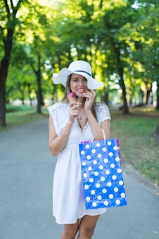 Belle fille avec chapeau blanc et sacs à provisions, manger des glaces dans la rue