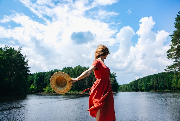 Belle fille avec un chapeau de paille près du lac. nature estivale incroyable. notion de voyage. inspiration pour l'envie de voyager. femme en robe rouge en lin. matériaux écologiques pour les vêtements.