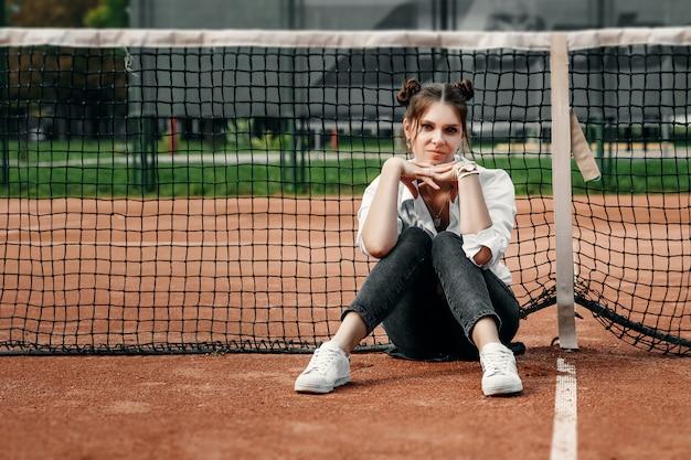 Une belle fille en chemise blanche, pantalon noir et baskets blanches s'assoit au filet sur le court de tennis.