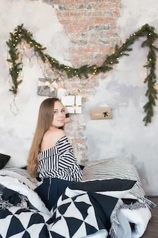 Belle fille en chemise est assise sur le lit près de l'arbre de noël et sourit