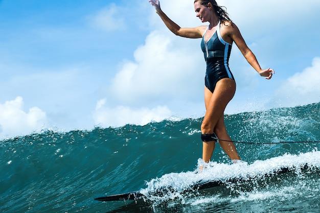 Belle fille à cheval sur une planche de surf sur les vagues
