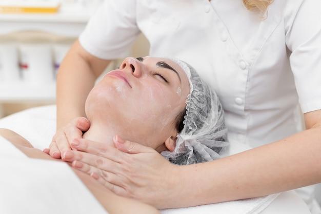 Belle fille chez l'esthéticienne fait les procédures de spa, massage du visage et masque pour la peau.