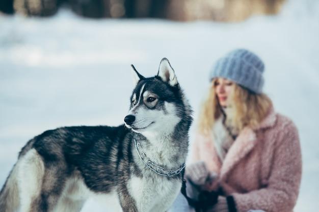 Belle fille avec un chien husky dans les bois enneigés