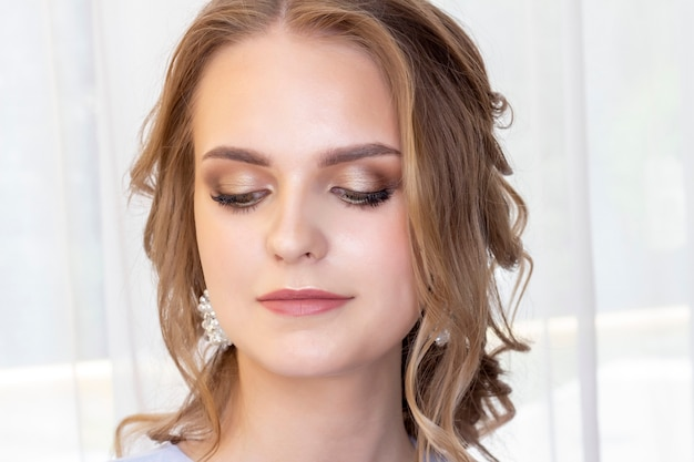 Belle fille avec une coiffure de mariage se regarde dans le miroir, portrait d'une jeune fille. beau maquillage. salon de beauté