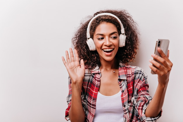 Belle fille avec une coiffure à la mode faisant selfie et agitant la main. heureuse dame noire en chemise à carreaux appréciant la chanson préférée.