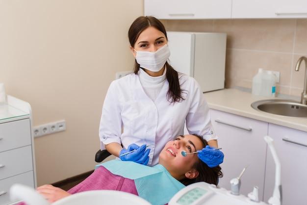 Belle fille en consultation avec un dentiste, traitement des caries.