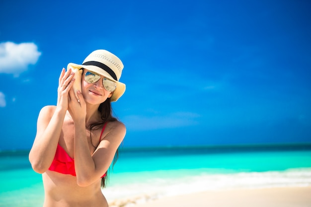 Belle fille avec coquillage dans les mains sur une plage tropicale