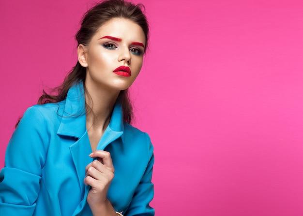 Belle fille en costume bleu sur fond rose avec maquillage créatif et style à la mode.