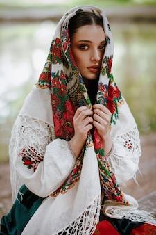 Belle fille en costume ethnique traditionnel avec une cape brodée sur la tête