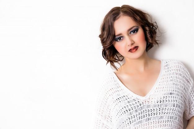 Belle fille avec coupe courte et maquillage avec des ombres bleues debout devant un fond blanc