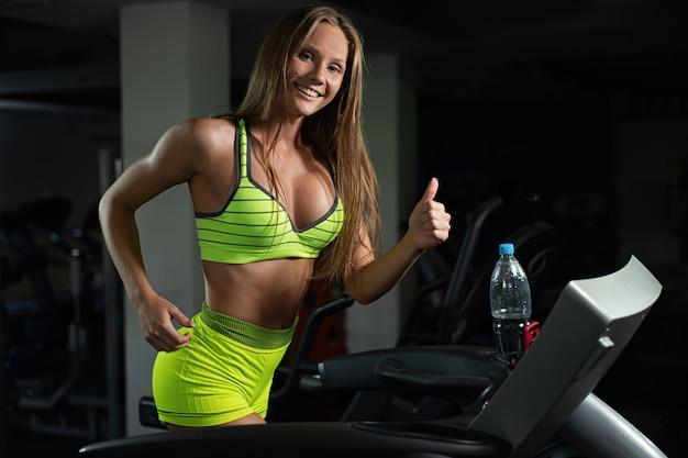 Belle fille en cours d'exécution sur tapis roulant dans la salle de gym