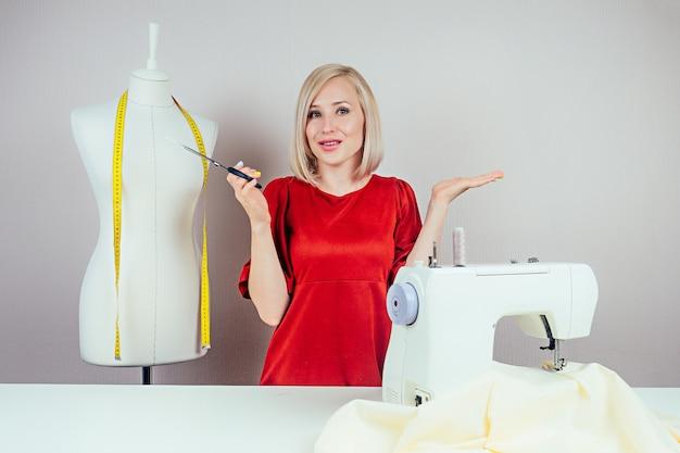 Belle fille couturière-créatrice-émotion de perplexité. sur le fond de la machine à coudre, du mannequin et du fond blanc.