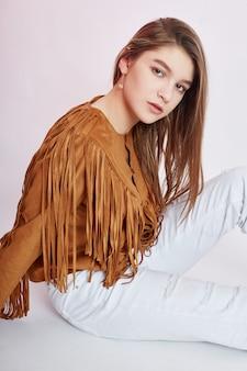 Belle fille de cow-boy en jeans blancs sur fond blanc. jeune adolescente