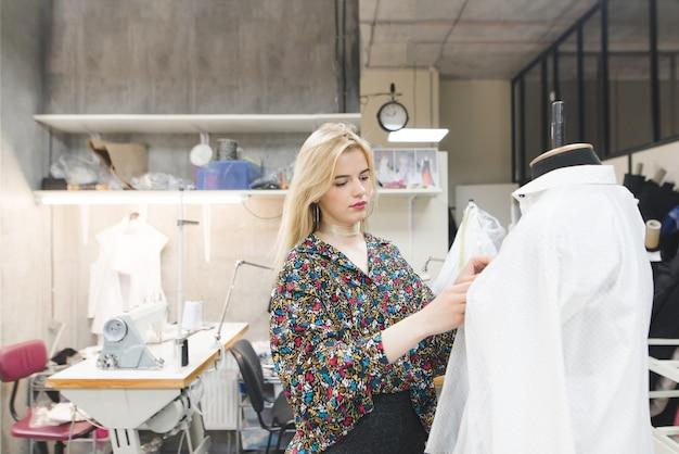 Une belle fille de créatrice de mode se tient dans un studio près du mannequin et y fixe des vêtements.