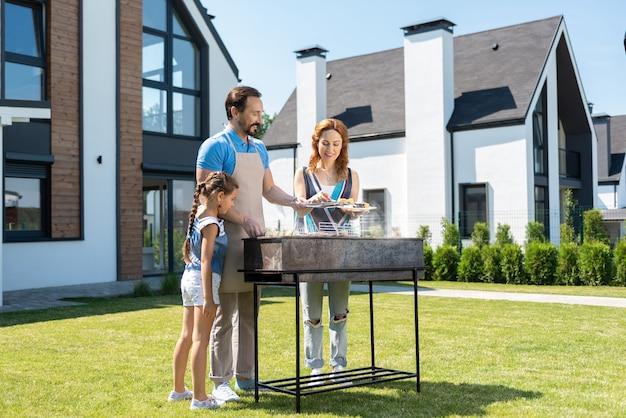 Belle fille curieuse debout avec ses parents tout en les aidant à préparer des légumes grillés