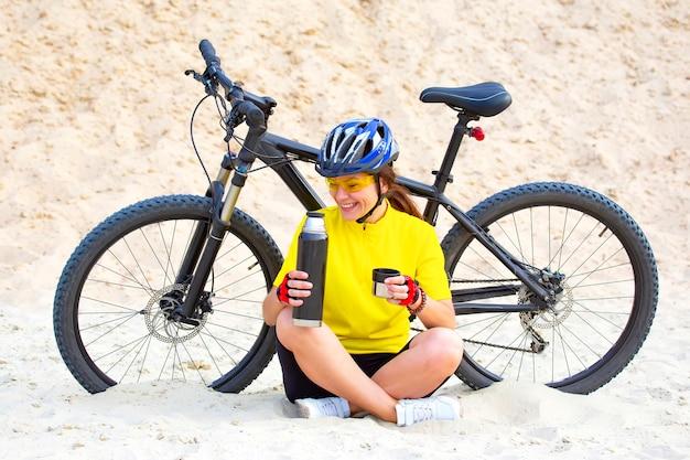 Belle fille cycliste verse le thé d'un thermos