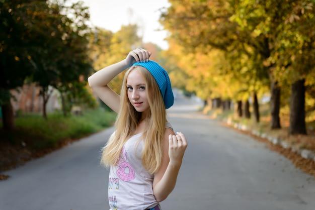 La belle fille dans un bonnet bleu sur la promenade