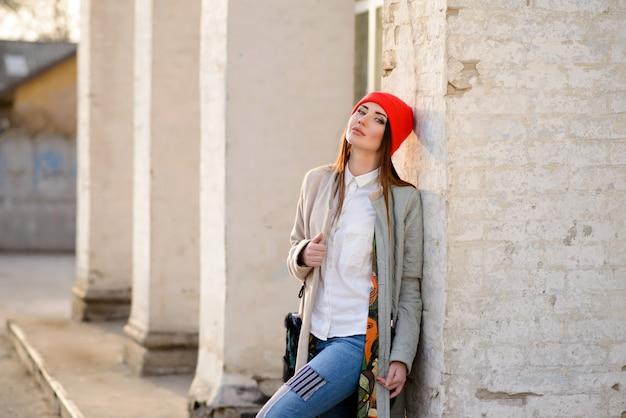 Belle fille dans un bonnet rouge se promène dans la ville