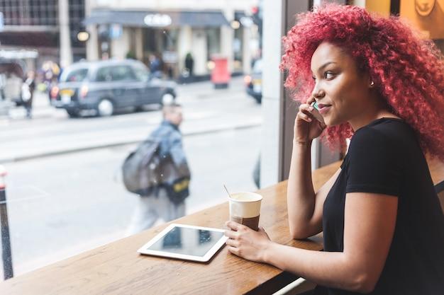Belle fille dans un café, parler au téléphone intelligent