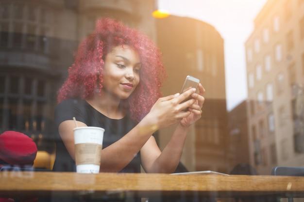Belle fille dans un café en tapant sur un téléphone intelligent