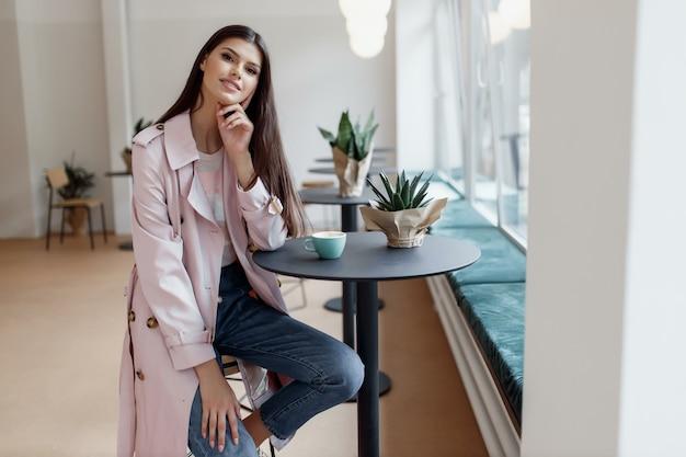 Belle fille dans un café avec une tasse de café
