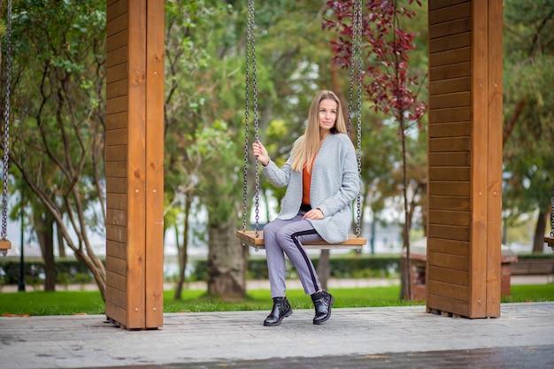 Belle fille dans un cardigan en tricot gris posant sur une balançoire