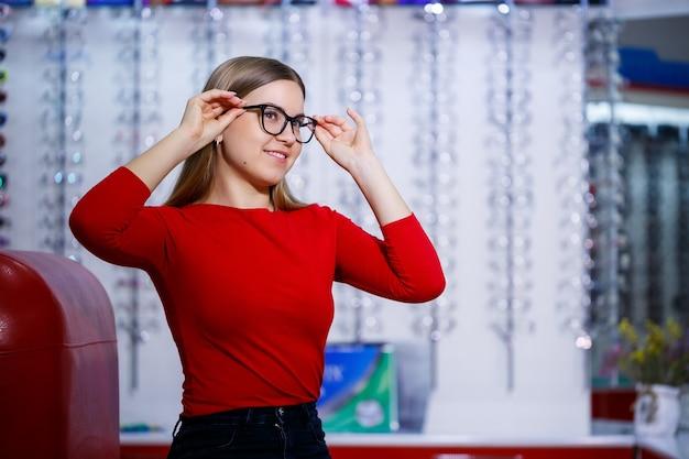 La belle fille dans un centre d'ophtalmologie prend des verres pour la correction de vision