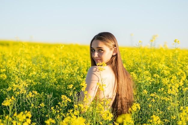 Belle fille dans un champ de colza, avec une épaule ouverte. photo de haute qualité