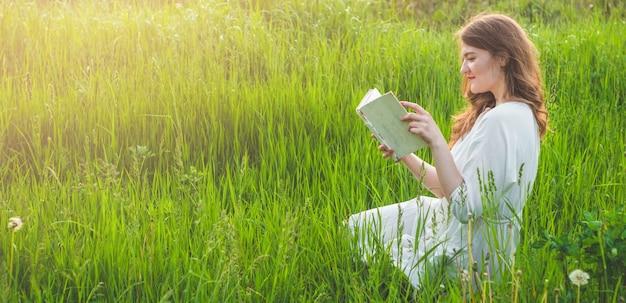 Belle fille dans le champ en lisant un livre. la jeune fille assise sur l'herbe, lisant un livre. repos et lecture