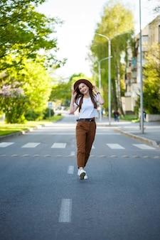 Une belle fille dans un chapeau marron et un t-shirt blanc marche sur la route par une chaude journée ensoleillée. belle jeune femme dans un chapeau avec un sourire sur son visage