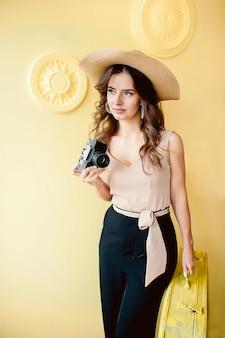Belle fille dans un chapeau de paille avec un appareil photo dans ses mains, sur un mur jaune une femme photographie
