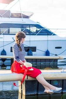 Belle fille dans un chapeau de paille sur le quai près des yachts de la mer et des bateaux.