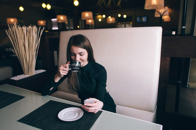 Une belle fille dans une chemise noire, boire du café dans un café